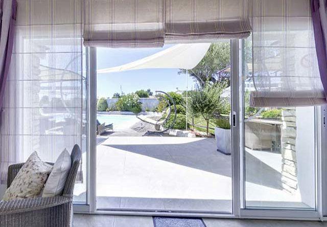 Baie vitrée du salon ouverte sur le patio